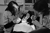 Dentists at work, London, 1981 - NLA - 1980s,1981,dental,Dental Nurse,dental nurses,dentist,Dentistry,dentists,employee,employees,Employment,job,jobs,LBR,London,people,practitioner,practitioners,staff,Work,work issues,worker,workers,workin