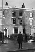 New Cross fire, where 13 young people died Deptford London 1981 . The blaze broke out inside the house, either accidentally or deliberately, during a birthday party at the house, Police guarding the b... - Peter Arkell - 1980s,1981,adult,adults,arson,attack,attacking,attacks,BAME,BAMEs,bigotry,Black,BME,bmes,building,BUILDINGS,burn,burning,BURNS,burnt,burnt out,cities,City,communities,community,death,deaths,destroyed,