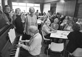 Day centre where the elderly pensioners meet, eat and socialise, South London 1981. Enjoying a sing song - Peter Arkell - 28-04-1981