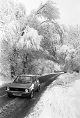 A car on slippy roads as Southern UK covered in snow, 1981 - Peter Arkell - 1980s,1981,AUTO,AUTOMOBILE,AUTOMOBILES,car,cars,CLIMATE,cold,cold snap,conditions,country,countryside,driver,drivers,driving,freezing,frozen,golf,hazard,hazardous,HAZARDS,ice,icy,low temperature,outdo