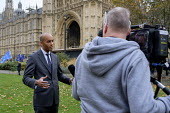 Chuka Umunna MP being interviewed, College Green, Westminster, London, on the day of four ministerial resignations over Brexit deal. - Philip Wolmuth - 2010s,2018,Brexit,camera,cameraman,cameras,Chuka Umunna,College,COLLEGES,communicating,communication,EU,Europe,European Union,filming,Houses of Parliament,interview,INTERVIEWED,INTERVIEWER,interviewin