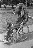 Man in a dog costume in a wheelchair. Event for dogs and their owners, London 1982 - NLA - 1980s,1982,animal,animals,bound,canine,cities,City,costume,costumes,disabilities,disability,disable,disabled,disablement,dog,dogs,dressed up,dressing up,fancy dress,incapacity,Leisure,LFL,LIFE,London,