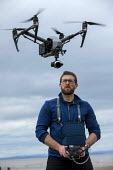 Pilot operating a DJI Inspire 2 Quadcopter drone, Weston Super Mare beach - Paul Box - 2010s,2018,air space,air transport,aircraft,beach,BEACHES,camera,cameras,COAST,Commercial Operations,communicating,communication,control,controls,device,devices,drone,drones,employee,employees,Employm