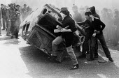 Rioting, The Bogside, Derry, Northern Ireland 1981. Youth turning a car over to make a burning barricade. IRA prisoner Bobby Sands had just died after a hunger strike - David Mansell - 06-05-1981
