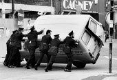 Rioting, The Bogside, Derry, Northern Ireland 1981. Highjacked stolen local butchers van is recovered by RUC police officers. IRA prisoner Bobby Sands had just died after a hunger strike - David Mansell - 1980s,1981,adult,adults,armed,arms,butchers,Catholic,Catholics,cities,City,Conflict,Conflicts,Derry,force,gun,guns,handgun,handguns,highway,hunger,INMATE,INMATES,IRA,Ireland,Irish,local,Londonderry,ma