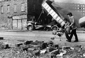 Rioting, The Falls Road, Belfast, Northern Ireland 1981. A mother walking past the toxic smoke from a smouldering highjacked lorry with her young son and child in a push chair. IRA prisoner Bobby Sand... - David Mansell - 1980s,1981,adult,adults,boarded up,Burning Barricade,Burnt Out,Catholic,Catholics,cities,City,Conflict,Conflicts,Devis Tower flats,disused,FAMILY,FEMALE,HAULAGE,HAULIER,HAULIERS,HGV,hgvs,highway,hunge