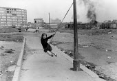Girls swinging on a rope from a lamp post, West Belfast 1981, Devis Tower flats, The Falls Road. IRA prisoner Bobby Sands had just died after a hunger strike - David Mansell - 1980s,1981,Catholic,Catholics,child,childhood,children,cities,City,Conflict,Conflicts,Devis Tower flats,female,females,flats,girl,girls,having fun,highway,hunger,INMATE,INMATES,IRA,irish,juvenile,juve
