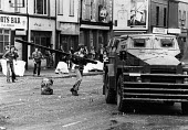 Rioters attacking an army armoured vehicle with a long plank, Falls Road, West Belfast Northern Ireland 1981 after the death of IRA prisoner Bobby Sands on hunger strike - David Mansell - 1980s,1981,adolescence,adolescent,adolescents,Armed Forces,armoured car,army,attack,attacking,British Army,Catholic,Catholics,cities,City,Conflict,Conflicts,death,DEATHS,died,highway,Humber,hunger,INM