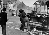 Army patrol, Rioting, The Bogside, Derry, Northern Ireland 1979 Riots after the Annual Londonderry Apprentice Boys parade - David Mansell - ,1970s,1979,adolescence,adolescent,adolescents,Annual Londonderry Apprentice Boys parade,Apprentice,APPRENTICES,apprenticeship,Armed Forces,armored vehicle,Armoured Land rover,army,bottle,bottles,BOY,