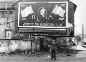West Belfast, Northern Ireland, 1981. Catholic boy celebrating in front of a advertising billboard: Victory to the Blanket Men POWs. The IRA prisoner Bobby Sands started his hunger strike on 1st March... - David Mansell - 1980s,1981,advertising,billboard,billboards,boy,boys,Catholic,Catholics,CELEBRATE,celebrating,child,childhood,children,cities,City,Conflict,Conflicts,flag,flags,hoarding,hunger,INMATE,INMATES,IRA,Irel