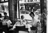 Mother and daughter having afternoon tea, Windsor 1961 - Romano Cagnoni - 1960s,1961,adult,adults,cake,cakes,catering,child,CHILDHOOD,CHILDREN,cities,City,daughter,DAUGHTERS,dessert,EBF,Economic,Economy,FAMILY,female,females,girl,GIRLS,hat,juvenile,juveniles,kid,kids,Leisur
