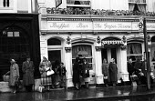 People waiting for a bus outside The Grapes Tavern Windsor 1961 in the rain - Romano Cagnoni - 1960s,1961,bag,bags,bought,bus,bus service,bus stop,buses,buy,buyer,buyers,buying,CHILD,CHILDHOOD,CHILDREN,CLIMATE,commodities,commodity,conditions,consumer,consumers,customer,customers,damp,EBF,Econo