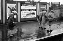 Schoolgirls walking home in the rain taking pigeon steps along the platform, Feltham Station, Hounslow, London - Romano Cagnoni - 1960s,1961,advertisement,advertisements,adverts,child,CHILDHOOD,children,CLIMATE,conditions,damp,EDU,educate,educating,Education,educational,female,females,game,girl,girls,home,journey,JOURNEYS,juveni
