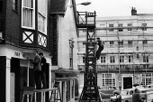 Worker climbing down from scaffolding Windsor 1961 no safety harness. The Castle Hotel - Romano Cagnoni - 1960s,1961,by hand,Castle,cities,City,climbing,danger,dangerous,descent,EBF,Economic,Economy,employee,employees,Employment,grip,H&S,hazard,hazardous,HAZARDS,health and safety,height,high up,Hotel,HOTE