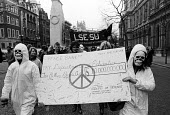 CND protest 1984 carrying a mocked up cheque contrasting the amount of money spent on arms as against education, opposite Ministry of Defence, Whitehall London - Stefano Cagnoni - peace movement,1980s,1984,action,activist,activists,against,banner,banners,Campaign for nuclear disarmament,CAMPAIGNING,CAMPAIGNS,carries,carry,carrying,cheque,CND,CND Symbol,costume,costumes,defence,