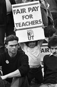 Young child holding a Fair Pay For Teachers placard London 1984 during protest NUT one day teachers strike - Stefano Cagnoni - 1980s,1984,activist,activists,against,CAMPAIGNING,CAMPAIGNS,child,CHILDHOOD,CHILDREN,DEMONSTRATING,demonstration,Fair,fair pay,industrial dispute,juvenile,juveniles,kid,kids,London,male,man,member,mem