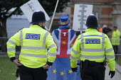 Police officers escorting anti Brexit campaigner Steve Bray out of the media encampment on College Green outside the Houses of Parliament as MPs start five days of debate on the withdrawal agreement w... - Philip Wolmuth - 2010s,2019,activist,activists,adult,adults,against,Brexit,Brexiters,CAMPAIGN,campaigner,campaigners,CAMPAIGNING,CAMPAIGNS,CLJ,College,COLLEGES,crime,DEMONSTRATING,demonstration,DEMONSTRATIONS,EU,Europ