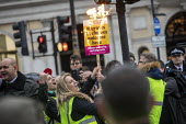 Right wing yellow vest pro Brexit protester burning a Stand Up to Racism placard whilst taunting the Britain is Broken - General Election Now, People's Assembly protest, Trafalgar Square, London - Jess Hurd - 12-01-2019