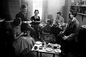 Science undergraduates from Newnham, KIngs and Caius College Cambridge 1959 talking and relaxing together at an afternoon tea party held in one of the student's rooms (L to R) Carol Deller, Michael Ho... - Kurt Hutton - 1950s,1959,accommodation,apartment,apartments,Cambridge,CHAT,chatting,College,COLLEGES,communicating,communication,companions,conversation,conversations,course,courses,degree,degrees,dialogue,discours