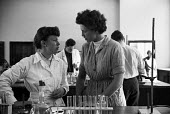 Girton College Cambridge 1959 Women Science students working together in the Lensfield Road laboratory, Margaret Scott (L) and Joan Fitton (R) - Kurt Hutton - 1950s,1959,Cambridge,collaboration,College,COLLEGES,communicating,communication,conversation,conversations,course,courses,degree,degrees,dialogue,discourse,discuss,discusses,discussing,discussion,EDU,
