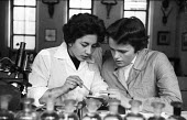 Girton College Cambridge 1959 Women Cancer research students examining bacetria, Zoology Department laboratory, Shireen Saleh (R)and Winnifred Peirce (L) - Kurt Hutton - 1950s,1959,bacteria,Cambridge,Cancer,CANCERS,College,COLLEGES,communicating,communication,conversation,conversations,course,courses,degree,degrees,Department,dialogue,discourse,discuss,discusses,discu