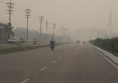 Amritsar, Punjab, India, air pollution. Late afternoon thick smog on the road to the Pakistan border. Air pollution in India is a serious issue with the major sources being fuelwood and biomass burnin... - Martin Mayer - 2010s,2018,Air Pollution,Air Quality,Amritsar,bike,bikes,BURN,burning,BURNS,cities,City,CONGESTED,congestion,ENI,environment,environmental degradation,Environmental Issues,fuel,highway,India,Low visib