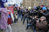 Photographers surrounding a young woman anti-Brexit protestor outside the Houses of Parliament as MPs vote on amendments to EU withdrawal deal, Westminster, London - Philip Wolmuth - 2010s,2019,activist,activists,against,Brexit,camera,cameras,CAMPAIGNING,CAMPAIGNS,DEMONSTRATING,demonstration,EU,Europe,European Union,FEMALE,group,groups,Houses,journalism,journalist,journalists,Lond