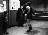 Nigerian boxer Dick Tiger in training at the gym watched by an older man and a young boy LIverpool 1958 - Alan Vines - 1950s,1958,African,Africans,ANIMAL,ANIMALS,BAME,BAMEs,Bedford Street gym,black,BME,bmes,box,boxer,boxers,boxes,boxing,boy,boys,child,CHILDHOOD,children,Dick Tiger,diversity,ethnic,ethnicity,exercise,e