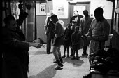 Nigerian boxer Dick Tiger centre in training at the gym watched by an older men and interested young boys LIverpool 1958 - Alan Vines - 1950s,1958,African,Africans,ANIMAL,ANIMALS,BAME,BAMEs,Bedford Street gym,black,BME,bmes,box,boxer,boxers,boxes,boxing,boxing gloves,boy,boys,child,CHILDHOOD,children,Dick Tiger,diversity,ethnic,ethnic