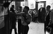 Nigerian boxer Dick Tiger in training at the gym watched by his trainers and young boys keen to follow in his footsteps LIverpool 1958 - Alan Vines - 1950s,1958,African,Africans,ANIMAL,ANIMALS,BAME,BAMEs,Bedford Street gym,black,BME,bmes,box,boxer,boxers,boxes,boxing,boxing gloves,BOY,boys,child,children,Dick Tiger,diversity,ethnic,ethnicity,exerci