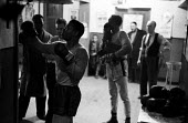 Nigerian boxer Dick Tiger in training at the gym watched by his trainers LIverpool 1958 - Alan Vines - 1950s,1958,African,Africans,ANIMAL,ANIMALS,BAME,BAMEs,Bedford Street gym,black,BME,bmes,box,boxer,boxers,boxes,boxing,Dick Tiger,diversity,ethnic,ethnicity,exercise,exercises,exercising,fitness,glove,