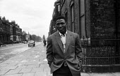 Nigerian boxer Dick Tiger walking along a street in LIverpool 1958 - Alan Vines - 1950s,1958,African,Africans,ANIMAL,ANIMALS,BAME,BAMEs,Bedford Street gym,black,BME,bmes,box,boxer,boxers,boxes,boxing,Dick Tiger,diversity,ethnic,ethnicity,exercise,exercises,exercising,fitness,Liverp