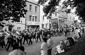 Durham Miners Gala 1986. MIners and their families from Sacriston Lodge parade back through the City after the traditional Labour movement rally on the Cricket Green on the day of The Big Meeting - Stefano Cagnoni - 1980s,1986,activist,activists,against,band,bands,banner,banners,brass band,CAMPAIGNING,CAMPAIGNS,communities,community,DEMONSTRATING,demonstration,DMA,Durham Miners Gala,male,man,march,marching,Meetin