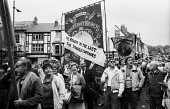 Durham MIners Gala 1986. One year after the end of the miners strike, mIners and their families from the KInsley Drift mine in Yorkshire display a defiant message on their banner on the traditional La... - Stefano Cagnoni - 1980s,1986,activist,activists,against,banner,banners,Big Meeting,CAMPAIGNING,CAMPAIGNS,communities,community,defiance,defiant,DEMONSTRATING,demonstration,display,displays,DMA,Durham Miners Gala,Kinsle