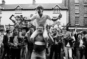 Durham MIners Gala 1986. Young people from the Durham coalfield commnities in an exuberant mood below Labour dignitaries on the balcony of the County Hotel on the traditional Labour movement parade th... - Stefano Cagnoni - 1980s,1986,activist,activists,against,alcohol,banner,banners,beer,Big Meeting,CAMPAIGNING,CAMPAIGNS,cheerful,communities,community,DEMONSTRATING,demonstration,DMA,drink,drinking,Durham Miners Gala,EMO