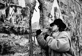 Young woman chipping away at the Berlin Wall 1989 on the West side, Berlin, Germany - Melanie Friend - 30-12-1989