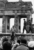 Young man jumping from the Berlin Wall 1989 as border guards still patrol, Berlin, Germany - Melanie Friend - 29-12-1989