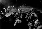 Celebrating on New Year's Eve 1989, The Brandenburg Gate by the Berlin Wall, Berlin, Germany. The first joint East German West German New Years Eve party. Woman in foreground waving at her son above o... - Melanie Friend - 31-12-1989
