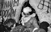 Woman climbing through a hole in the Berlin Wall 1989 from the East to the West side, New Year's Eve, Berlin, Germany - Melanie Friend - 31-12-1989