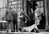 Landed gentry outside large country house Buckinghamshire 1961 - Romano Cagnoni - 1960s,1961,AFFLUENCE,AFFLUENT,animal,animals,aristocracy,aristocrat,aristocrtes,Bourgeoisie,Bowler Hat,bowler hats,canine,cities,City,dog,dogs,elite,elitism,EQUALITY,FEMALE,high,high income,house,hous