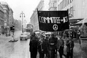 Committee of 100 Action for LIfe London 1961 protest for nuclear disarmament marching along Oxford Street in pouring rain - Romano Cagnoni - peace movement,1960s,1961,activist,activists,against,Anti War,Antiwar,atomic,CAMPAIGN,Campaign for nuclear disarmament,campaigner,campaigners,CAMPAIGNING,CAMPAIGNS,cities,City,cnd,CND Symbol,Committee