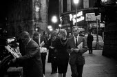 Smartly dressed couple passing newspaper seller in late evening Piccadilly Circus, West End, London 1961 - Romano Cagnoni - 11-09-1961