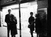 Young people outside Jazz club 1961 near Piccadilly Circus, West End, London - Romano Cagnoni - 1960s,1961,ace,adult,adults,cities,City,club,clubs,couple,COUPLES,culture,entertainment,evening,FEMALE,leisure,LFL,LIFE,lights,London,MATURE,melody,mod,mods,music,MUSICAL,night,night out,night time,ni