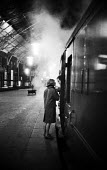 Couple saying goodbye Kings Cross Station London 1961 as late night steam train prepares to leave - Romano Cagnoni - 1960s,1961,adult,adults,boyfriend,BOYFRIENDS,carriage,carriages,cities,City,communicating,communication,conversation,conversations,couple,COUPLES,departing,departure,dialogue,discourse,discuss,discuss