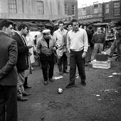 Richard Burton playing football on film set of Look Back in Anger, 1959 Producer Harry Saltzman (L) a street market in Romford - Romano Cagnoni - 28-03-1959