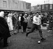 Richard Burton playing football on film set of Look Back in Anger, 1959 a street market in Romford. Mary Ure, Gary Raymond (L) Producer Harry Saltzman - Romano Cagnoni - 28-03-1959