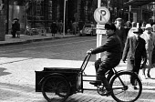 Cyclist with delivery on High Street Helsinki Finland 1961 - Romano Cagnoni - 1960s,1961,bicycle,bicycles,BICYCLING,Bicyclist,Bicyclists,BIKE,BIKES,bought,business,buy,buyer,buyers,buying,caution,cities,City,commodities,commodity,consumer,consumers,customer,customers,cycle,cycl