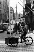 Cyclist with delivery on High Street Helsinki Finland 1961 - Romano Cagnoni - 1960s,1961,bicycle,bicycles,BICYCLING,Bicyclist,Bicyclists,BIKE,BIKES,bought,business,buy,buyer,buyers,buying,cities,City,commodities,commodity,consumer,consumers,customer,customers,cycle,cycles,cycli