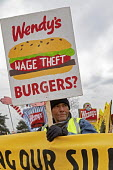 Ypsilanti, Michigan USA: Coalition of Immokalee Workers protest at a Wendy's fast food restaurant, asking the company to pay more for the Florida tomatoes to improve wages for Florida farmworkers, who... - Jim West - 2010s,2019,activist,activists,against,AGRICULTURAL,agriculture,BAME,BAMEs,banner,banners,BME,bmes,boycott,boycott Wendy's,burger,burgers,CAMPAIGNING,CAMPAIGNS,catering,CIW,Coalition,Coalition of Immok