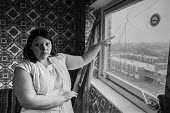 Housing problems, London 1983 a woman pointing to a broken window in her North Woolwich high rise flat - NLA - 06-01-1983